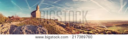 Romanesque church Saint Michael Drazovce village and industrial park Nitra - North in sunset Slovak republic. Autumn panoramic scene. Landscape in middle Europe. Retro photo filter.