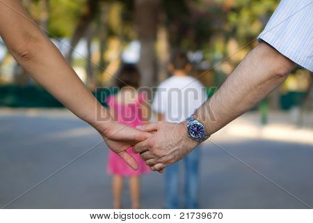 Parents Holding Hands With Kids In Front