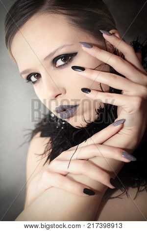 Glamorous matte black gray makeup and manicures on a sharply oval-shaped nails with feathers of a model on a grey background.