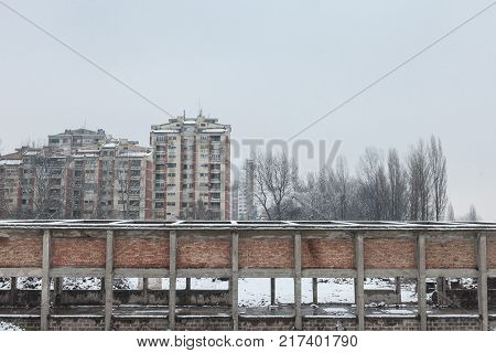 Communist housing buildings in front of an abandoned warehouse in Pancevo Serbia during a cold afternoon under the snow.