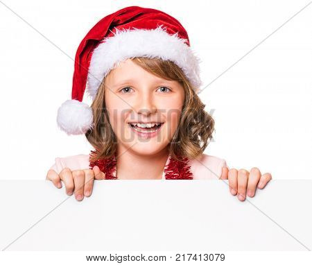 Little girl wearing Santa Claus hat, posing behind white panel isolated on white background. Kid holding empty Christmas billboard. Child peeping behind blank holidays board.