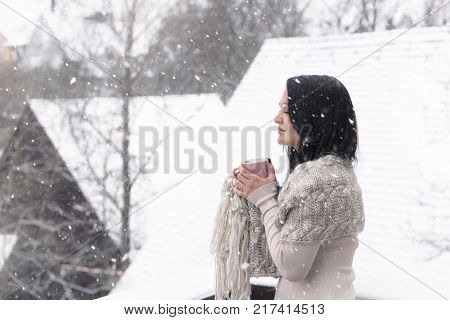 Woman with hot drink under snowfall - Beautiful young brunette woman in a cozy sweater and a shawl holding a cup of hot drink enjoying the falling snowflakes with her eyes closed.