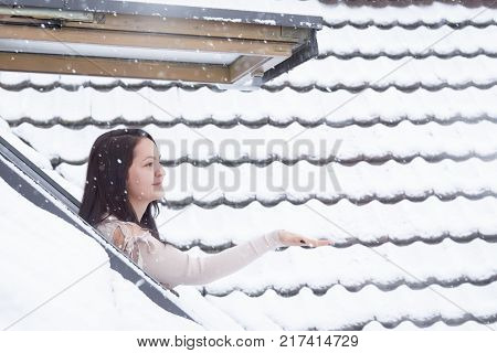 Woman reaching snowflakes through roof window - Attractive brunette woman dressed in a cozy sweater standing outside on her window reaching her hand to catch the snowflakes.