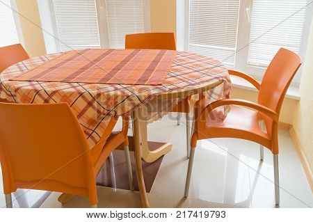 Four orange chairs and table with checkered tablecloth in the dining room