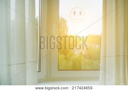 Window in the interior with curtains, on the glass drops of rain and a positive smiley