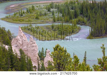 Hoodoos on Tunnel Mountain trail in Banff National Park with Bow River in the background. Hoodoos are composed of sedimentary rock and harder rock underneath. Once softer sediment erodes rock needle or tower-like natural obstacles are left.