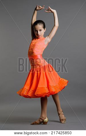 Girl dancer 9 years old ballroom dancing poses on a gray background.