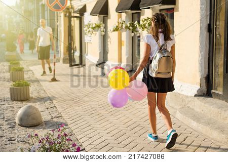 Back view,  Girl teenager high school student with balloons, in school uniform with glasses goes along the city street. Start of classes.