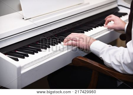 Male hands creating music on white piano background. Music performers hands with white cuffs playing piano. White piano with black keyboard and musicians hands. Piano player concept.