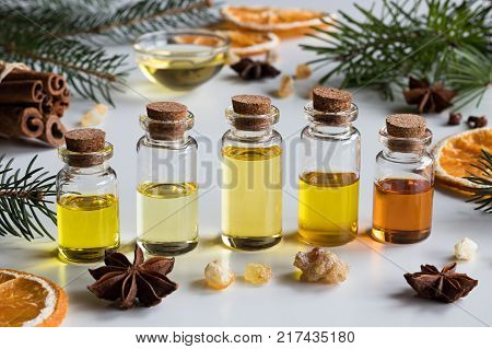 Selection of essential oils with Christmas spices and ingredients: bottles of essential oil spruce fir frankincense resin star anise cinnamon dried orange slices.
