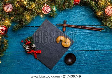 Photo of New Year branches of fir, black board, sticks for sushi, cookies with prediction on blue wooden background