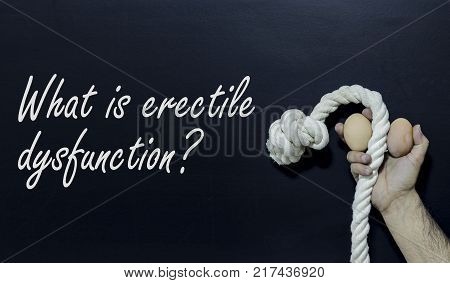 Written text: What is erectile dysfunction Man holding rope and two eggs as symbol of male penis on black surface