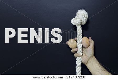 Written text: Penis. Man holding rope and two eggs as symbol of male penis on black surface