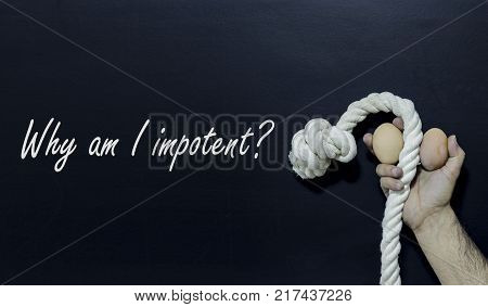 Written text: Why am I impotent. Man holding rope and two eggs as symbol of male penis on black surface