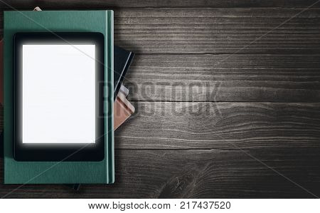 glowing ebook-reader on stack of books on rustic wooden desk