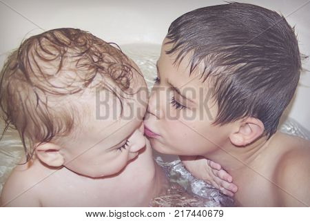 Big brother plays with little brother in the bathroom and kisses him on the cheek. Toning