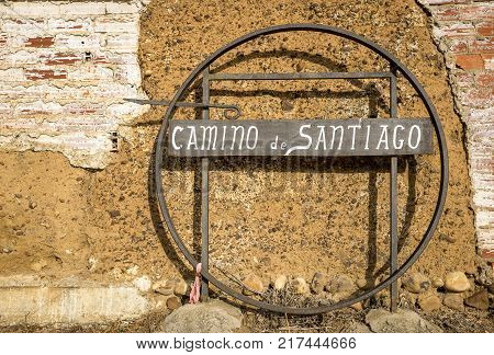 Camino de Santiago, Way of Saint James signpost on a metallic plate against an old wall