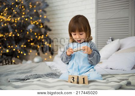 Small cute little girl is 2 years old sitting near Christmas tree and looking at the calendar. 31th of December. New Year's Eve