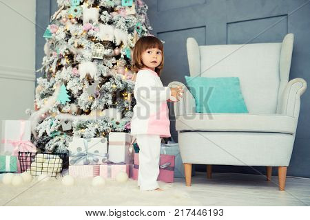 Emotional smiling little girl in pajama with Christmas gifts near New Year's tree and decorated fireplace.