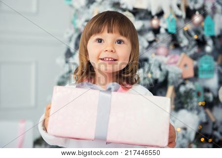 New Year's gift, emotions of happiness and joy. Little smiling girl gives a gift. Close-up. In the interior