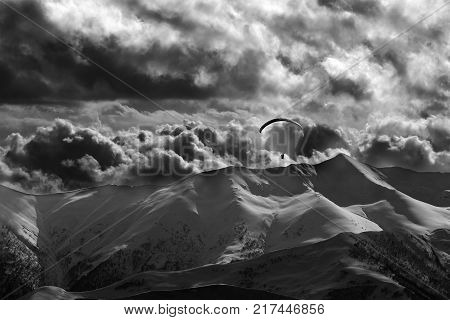 Evening mountain with clouds and silhouette of parachutist. Caucasus Mountains. Georgia region Gudauri. Black and white toned landscape.