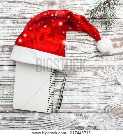Wooden background. White. Winter card. His Santa's hat. Green fir branches. Xmas card. Letter for a Christmas or New Year greeting card. Stylish modern. With snowflakes Xmas and Happy New Year composition. Flat lay, top view