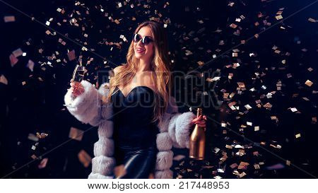 Well-dressed pretty woman in sunglasses drinking champagne and standing in falling confetti.