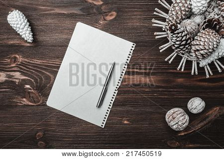 Brown wood background with texture. Cones and decorative walnuts. Letter to Santa's message and holidays. Counter Strikes. Holiday card. Xmas and Happy New Year composition. Flat lay, top view