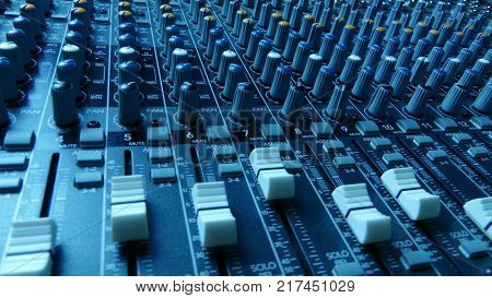 Mixing console. Audio mixer faders and knobs.