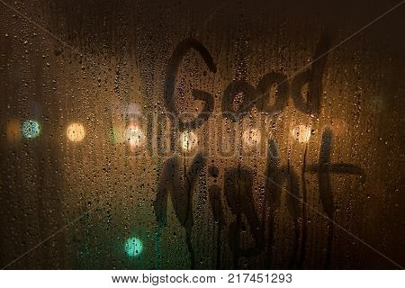 the inscription good night on the wet glass at night on the unfocused background