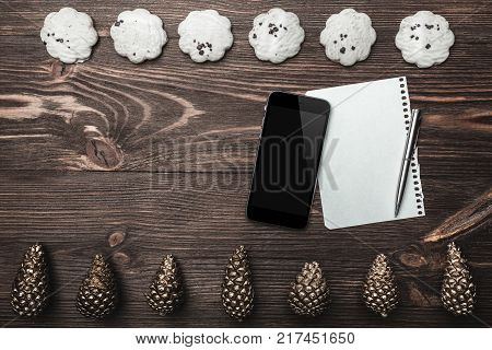Brown wood background. Gold cones and sweet biscuits arranged diametrically opposed. Letter and phone, space for a greeting message. Top View. With Christmas.