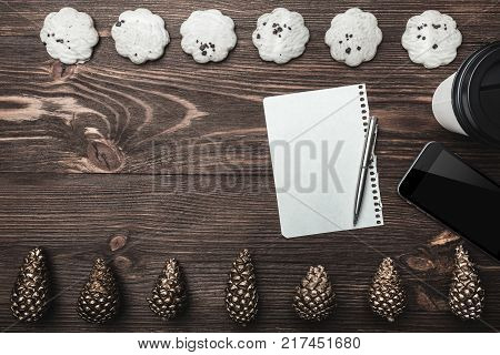 Brown wood background. Gold cones and sweet biscuits arranged diametrically opposed. Letter, telephone and coffee, space for a greeting message. Top View.