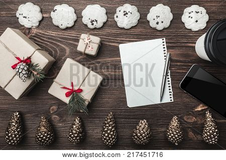 Brown wood background. Gold cones and sweet biscuits arranged diametrically opposed. Letter, phone, star, coffee and gifts, space for a greeting message. Top View.