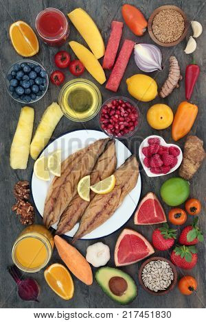 Super food for a healthy heart concept with smoked mackerel, fruit, vegetables, seeds, juice, herbs, spice and olive oil on marble. Health food high in omega 3,  anthocyanins, fiber and antioxidants.
