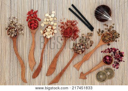 Chinese herbal medicine with herbs in wooden spoons, acupuncture needles and moxa sticks used in moxibustion therapy with feng shui coins on bamboo background. Top view. poster
