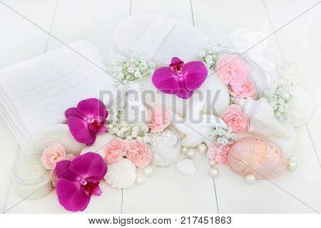 Beauty treatment cleansing and spa ex foliation products with orchids and carnation flowers, salt, moisturising cream, body lotion, seashell soaps, sponges, wash cloths, shells and decorative pearls