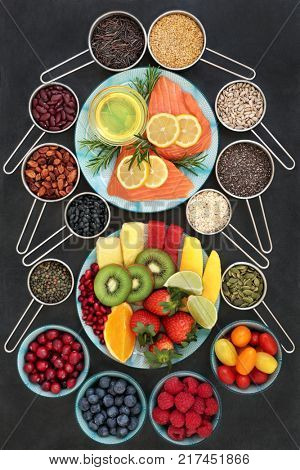 Super food for a healthy heart concept with foods high in omega 3 fatty acids, antioxidants, anthocyanins and vitamins. Fruit, vegetables, seeds, nuts, pulses, cereals, grains, herbs and olive oil.