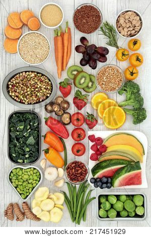 Vegetarian superfood concept of fresh fruit, vegetables, cereals, grains, pulses, herbs and spice. Health food with foods high in antioxidants, minerals, vitamins, fiber, smart carbs and protein.