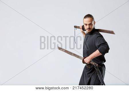 A young ninja man in a black uniform stands sideways with two swords. One holds his neck behind the other horizontally in front of him on a gray background