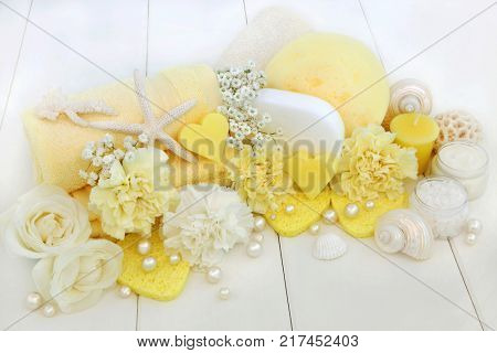 Beauty treatment cleansing and spa accessories including ex foliating salt, moisturising cream, heart shaped soaps, sponges, rose and carnation flowers.
