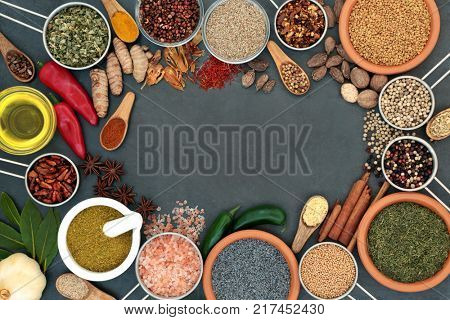 Herb and spice abstract background border with dried herbs and spices on slate. Top view.