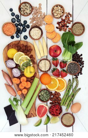 Healthy diet food for weight loss with fresh fruit, vegetables, nuts, seeds, grains, cereals and dairy with herbs used as an appetite suppressant. Top view on rustic background.