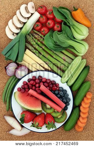 Health food for healthy eating concept with fresh vegetables and fruit on cork background, high in antioxidants, anthocyanins, minerals, vitamins and dietary fiber. Top view.