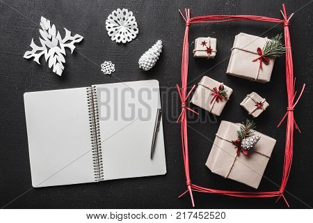 On the black background, many gifts and handmade items, a booklet where you can leave a greeting message. Top view.