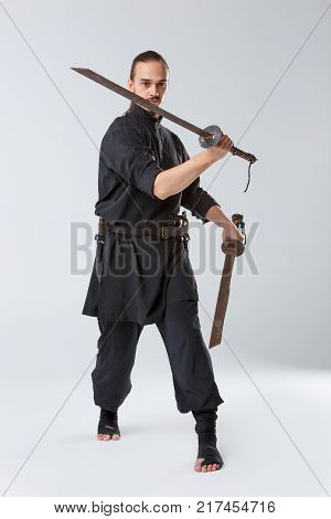 A ninja man in black uniform with two swords. Holds one sword in front of him on a gray background