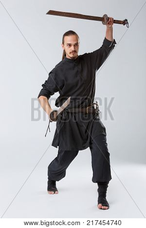 A ninja male in black uniforms coaches both attack and defense with two swords. One is raised horizontally upward by another, attacking against a gray background