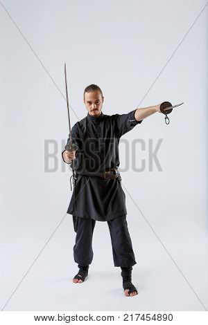 A black ninja man holds two swords in his hand. One is directed forward another vertically in front of him on a gray background. Front view