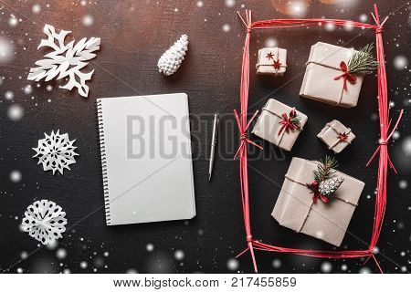 Christmas greeting card, black background, handmade gifts in a red rectangle. Letter white, where you can leave a holiday message, fir tree with snowflake effect.