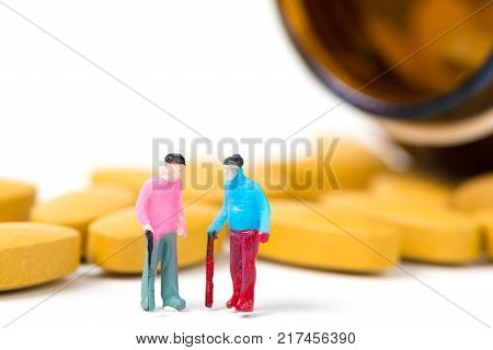 Miniature People, Small Figure Old Man Or Patient Holding Walking Stick With Vitamin C Pill Or Table