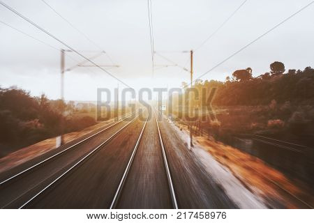 View from cabin of high-speed suburban train on sunset: railway tracks going to vanishing point autumn grasslands trees pillars wires sun flare and trees; strong motion blur